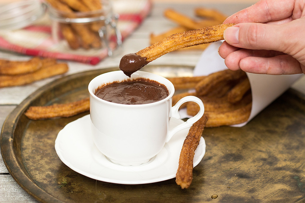 A cup filled with warm chocolate is the perfect match for a hot, cinnamon churro on a cold day.