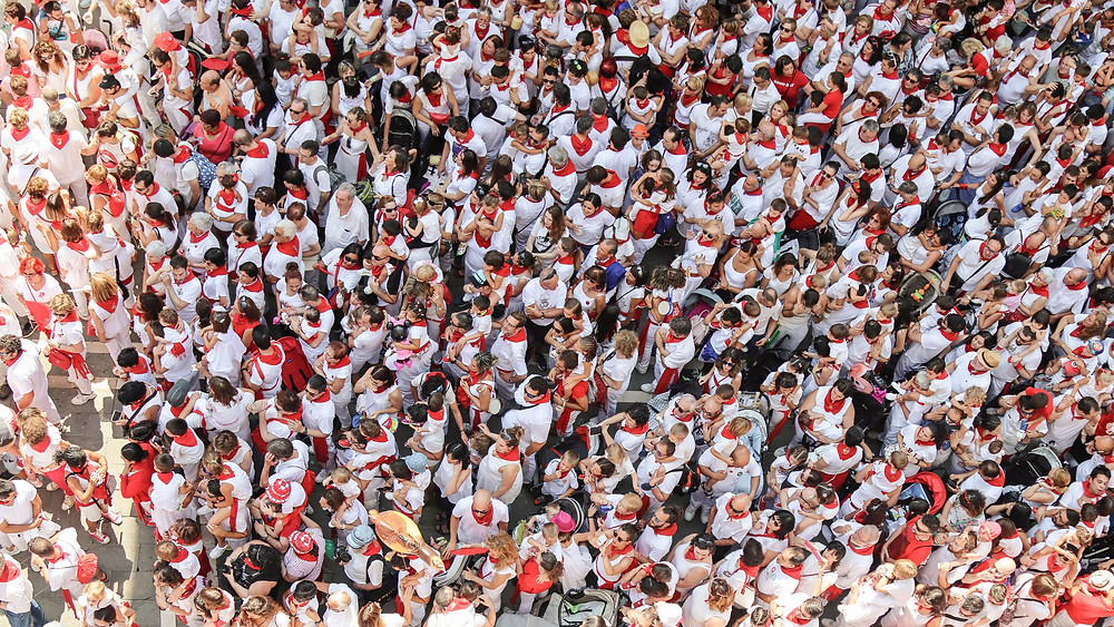 Locals and Tourists in the traditional red scarves during Pamplona Running of the Bulls