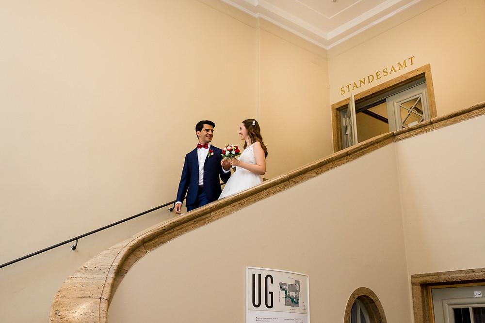 Brautpaar geht die Treppe des Standesamtes Schöneberg in Berlin hinunter