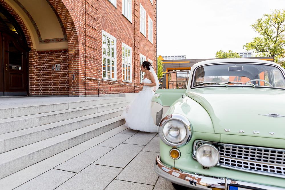 Braut geht aus dem Auto Richtung zur Trauung