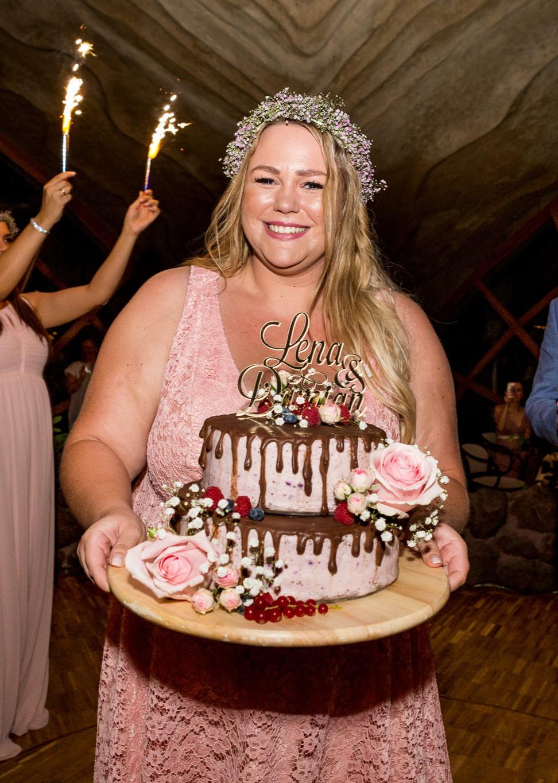 Trauzeugin haltet die Hochzeitstorte fest