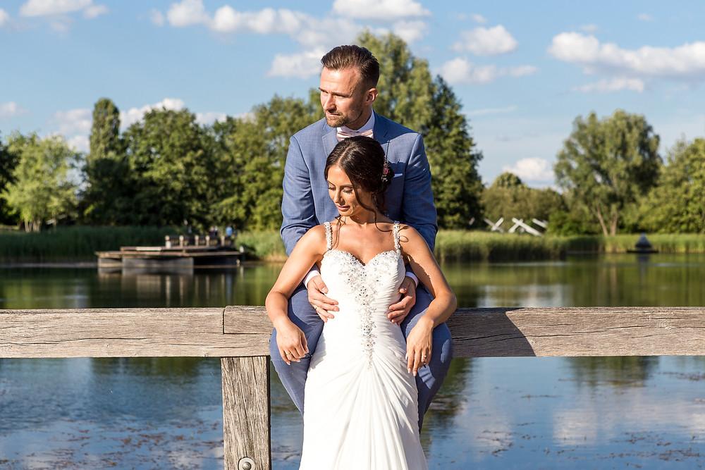 Brautpaar auf einen Zaun mit See und Grün in der Hintergrund