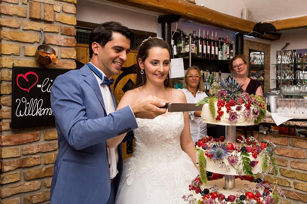 Brautpaar schneidet die Hochzeitstorte an beim Restaurant Landhaus im Botanischer GartenLandhaus