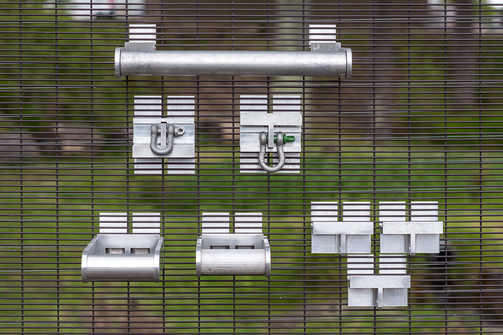 Some of QAB System's fencing quick access brackets for perimeter security maintenance and installation attached to 358 mesh security fencing panel