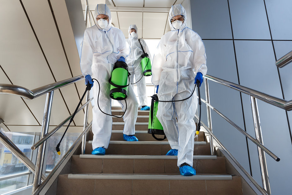 People wearing protective suits disinfec