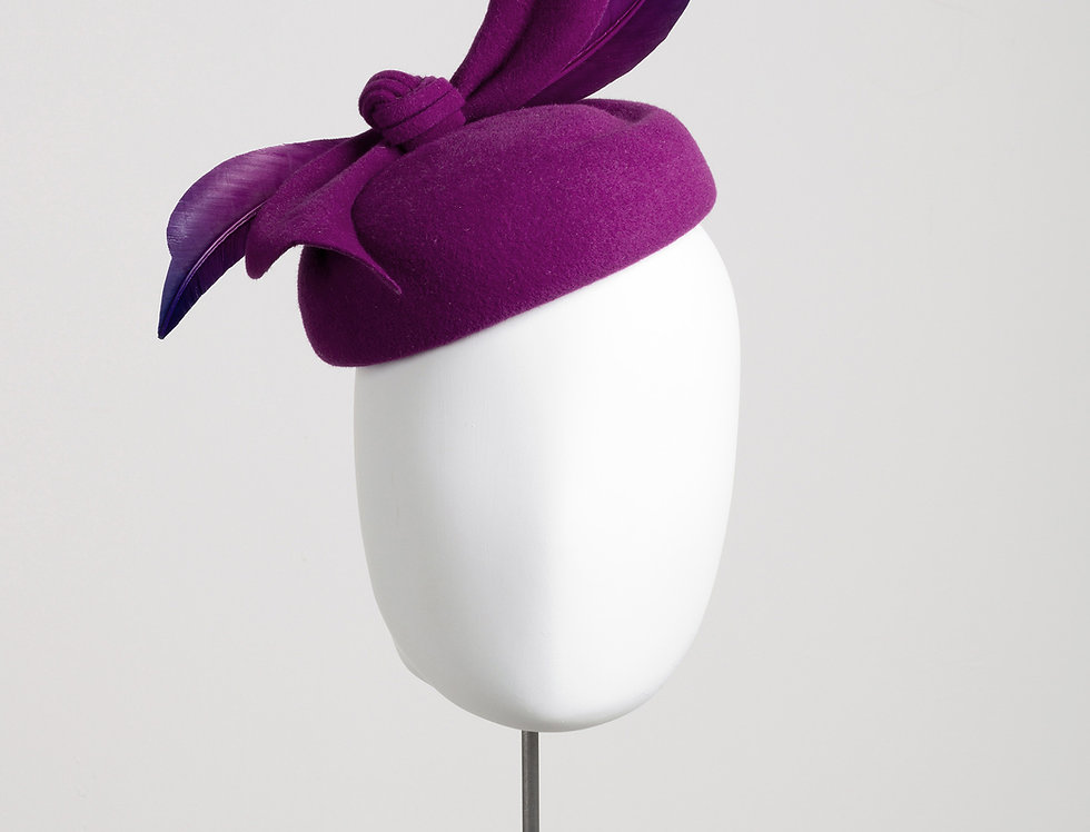 large felt pillbox hat with curved groove detail and sculptural bow - front view