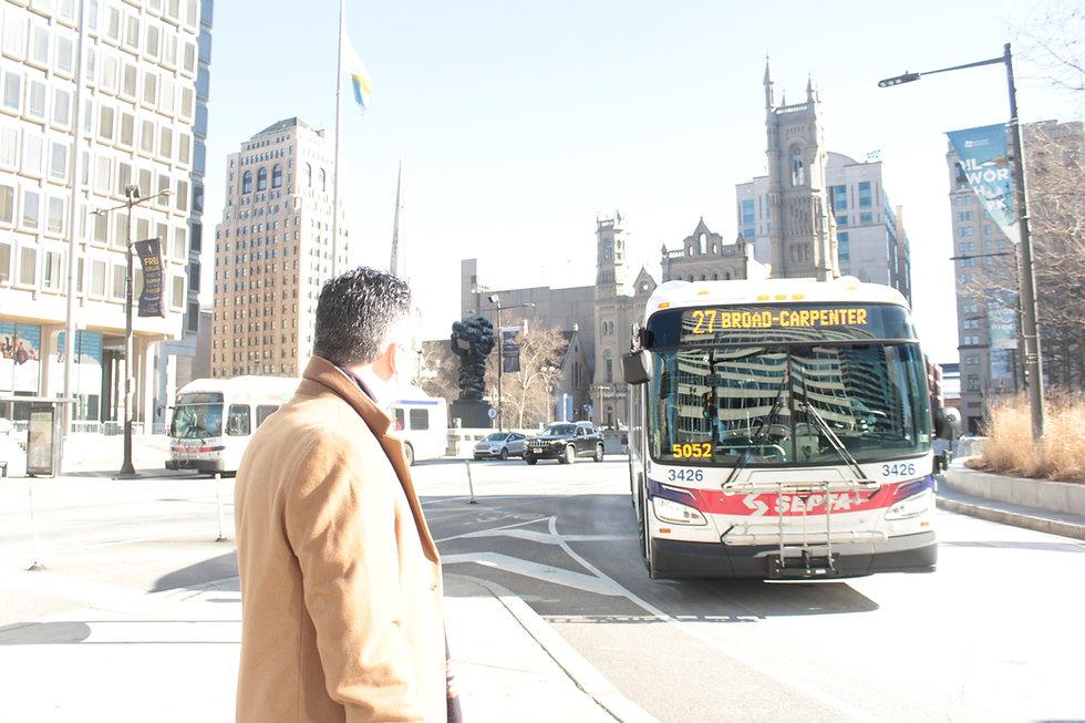 Judge Dan Sulman walking in Dilworth Park as a SEPTA bus passes by
