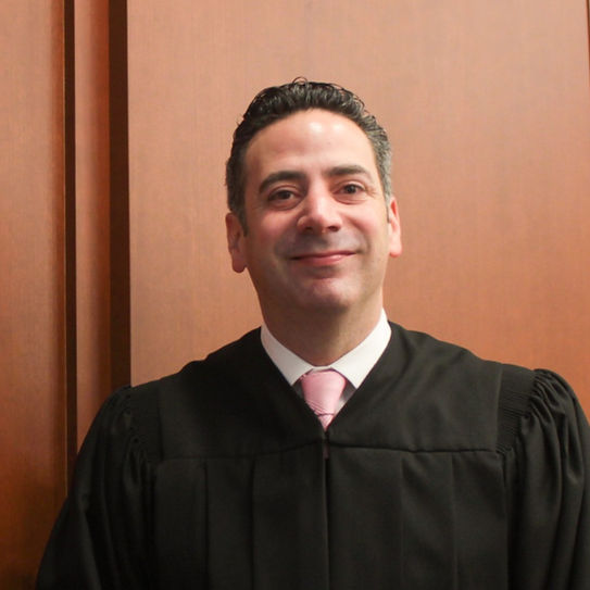 Judge Dan Sulman in his robes standing behind his bench in the Philadelphia Family Court