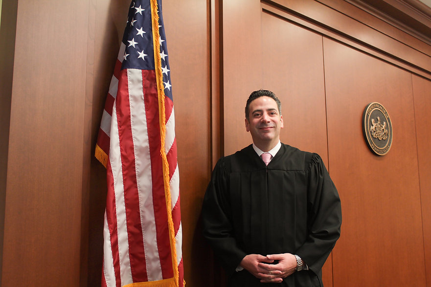 Judge Dan Sulman standing in his robes next to an American flag and flanked by the Seal of the Commonwealth of PA