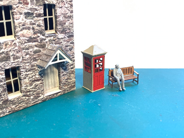 Model cottages with old phone box and man sitting on bench