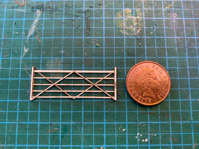 4mm scale 5 bar gate made from 3 layers of laser-cut card next to a penny.
