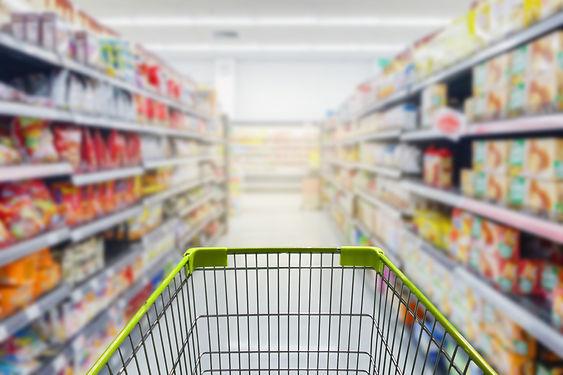 Supermarket aisle with empty green shopp
