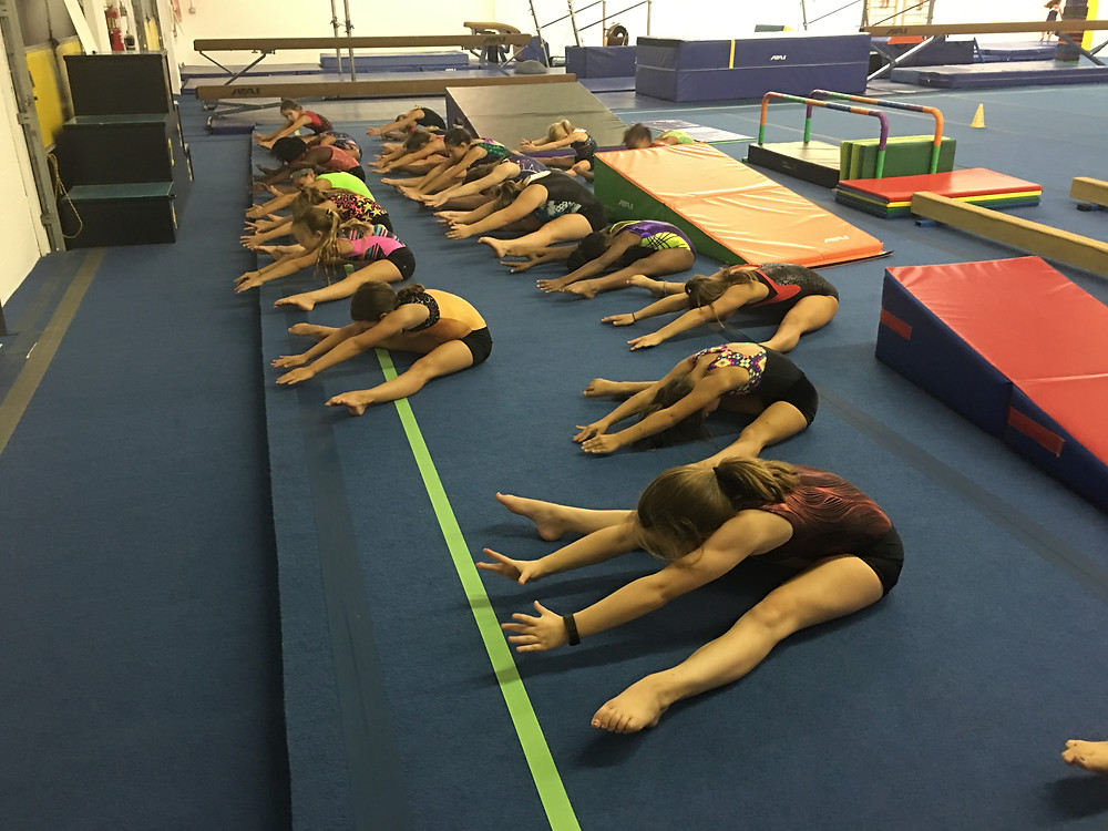 Copper Team stretches out their straddle positions.