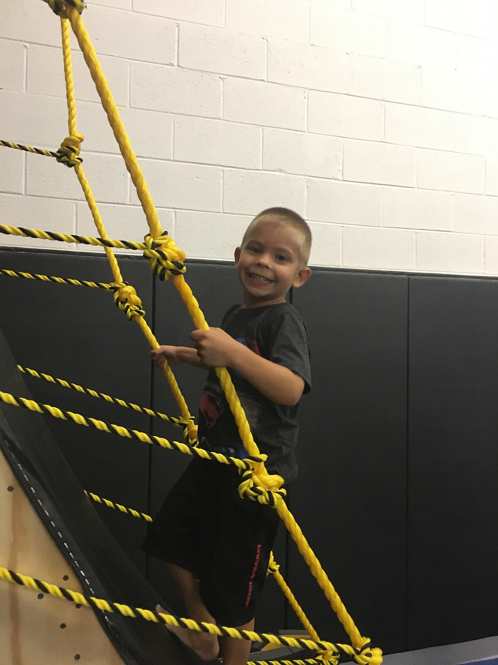 Bee Strong Boy class member, Nicholas, uses ropes to help ascend the warped wall.