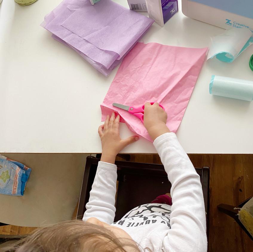 Daughter cutting paper
