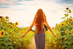 Girl with red hair in sun flower field