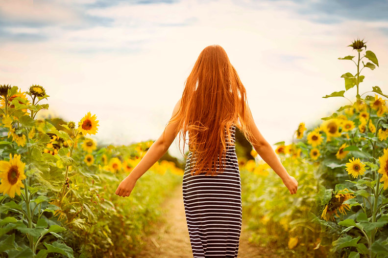 Girl with red hair in sun flower field.j