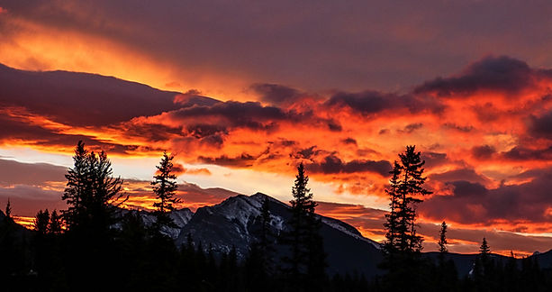 Majestic night sky with deep orange and purple colors and setting sun over mountain peak