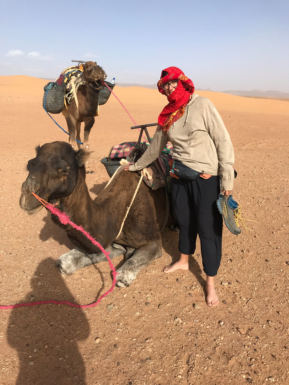 woman in turban with camels sahara desert