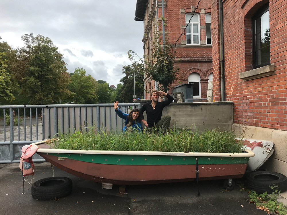 Two people pose behind a garden boat in Tubingen Germany.