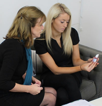 Kate discusses a laser hair removal treatment with a client in her salon in Reading, Berkshire