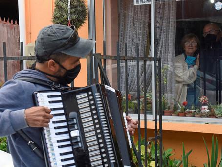 Un chileno toca el acordeón frente a la ventana de sus padres para animarlos en la cuarentena por el