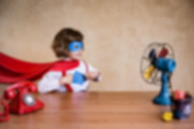 Portrait of child businessman superhero in office.jpg