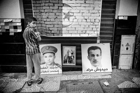 Aux pieds du garçon, le portrait du colonel Mohamed Chaabani, nationaliste condamné à mort et exécuté en 1964 pour trahison, réhabilité en 1984, et celui de Didouche Mourad, cofondateur du Front de libération nationale (FLN) en 1954.