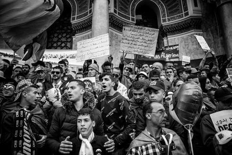 Manifestants, esplanade de Grande Poste d'Alger. Leurs pancartes critiquent le chef d'état-major de l'Armée nationale populaire, qualifient le gouvernement d'illégal et dénoncent un blocus de la capitale ne permettant pas aux manifestants extérieurs d'y pénétrer. Lieu emblématique de rassemblement, les escaliers de la Grande Poste ont été fermés fin mai 2019.