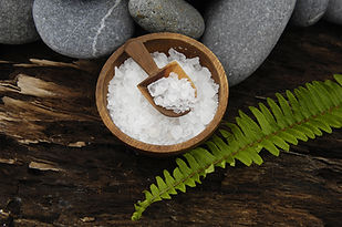 herbal salt in bowl and stones with fern