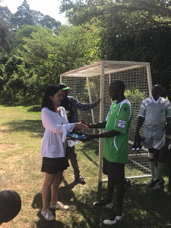 The Huruma Slum Men's Football Team are given a pair of boots each. - 2017
