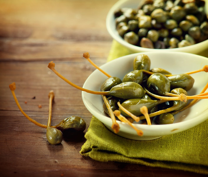Capers closeup on wooden table.jpg