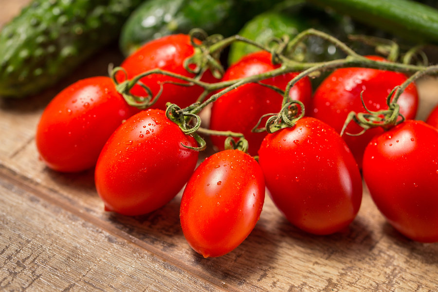 Group of plum Roma tomatoes ripe on a vi