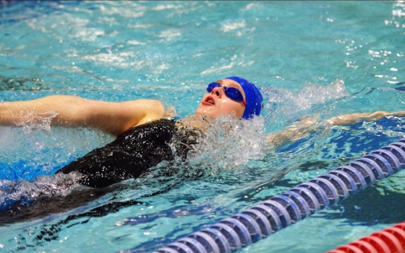 Juliette swims backstroke for her high school varsity swim team, West Potomac