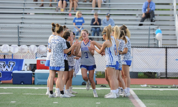 Juliette runs out onto the lacrosse field greeted by her teammates!