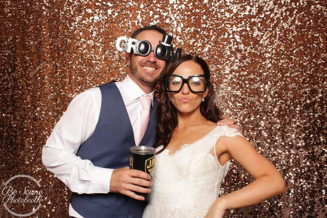 Bride & Groom taking pictures in the Be Scene Photo Booth