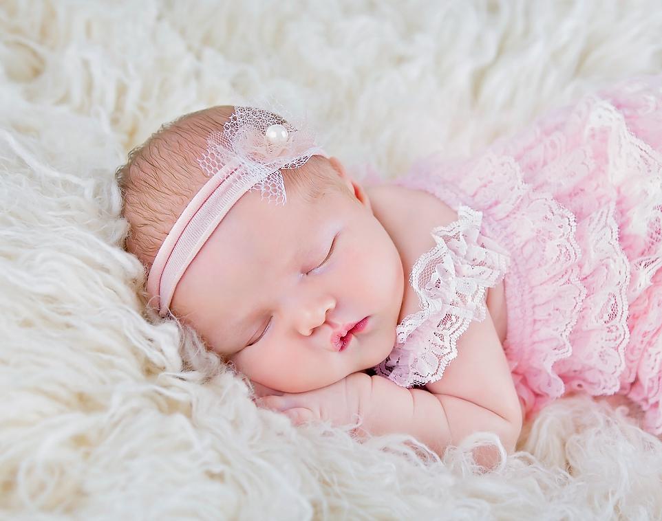 Newborn baby girl in pink romper
