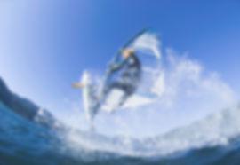 Healthy man windsurfing on the ocean