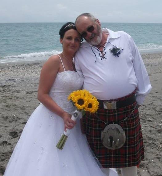 daughter standing with her dad on the beach after her wedding