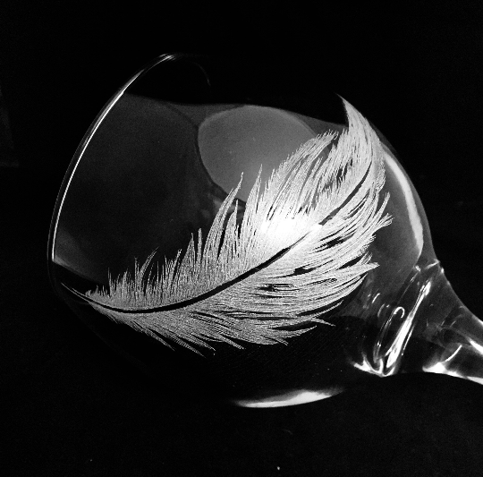a feather engraved on to a gin glass