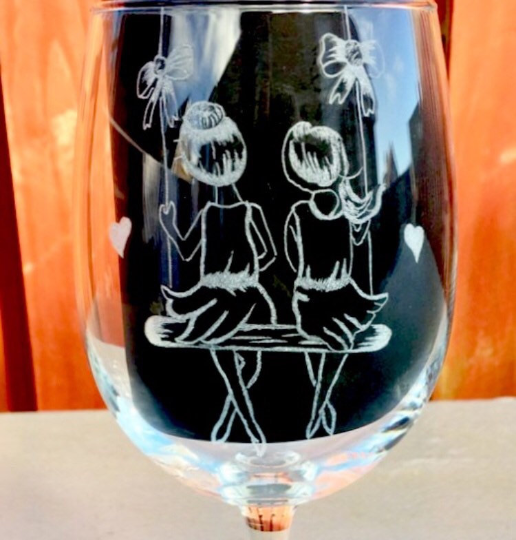 two girls hand engraved on to a wine glass, girls are sitting on a swing facing away from you