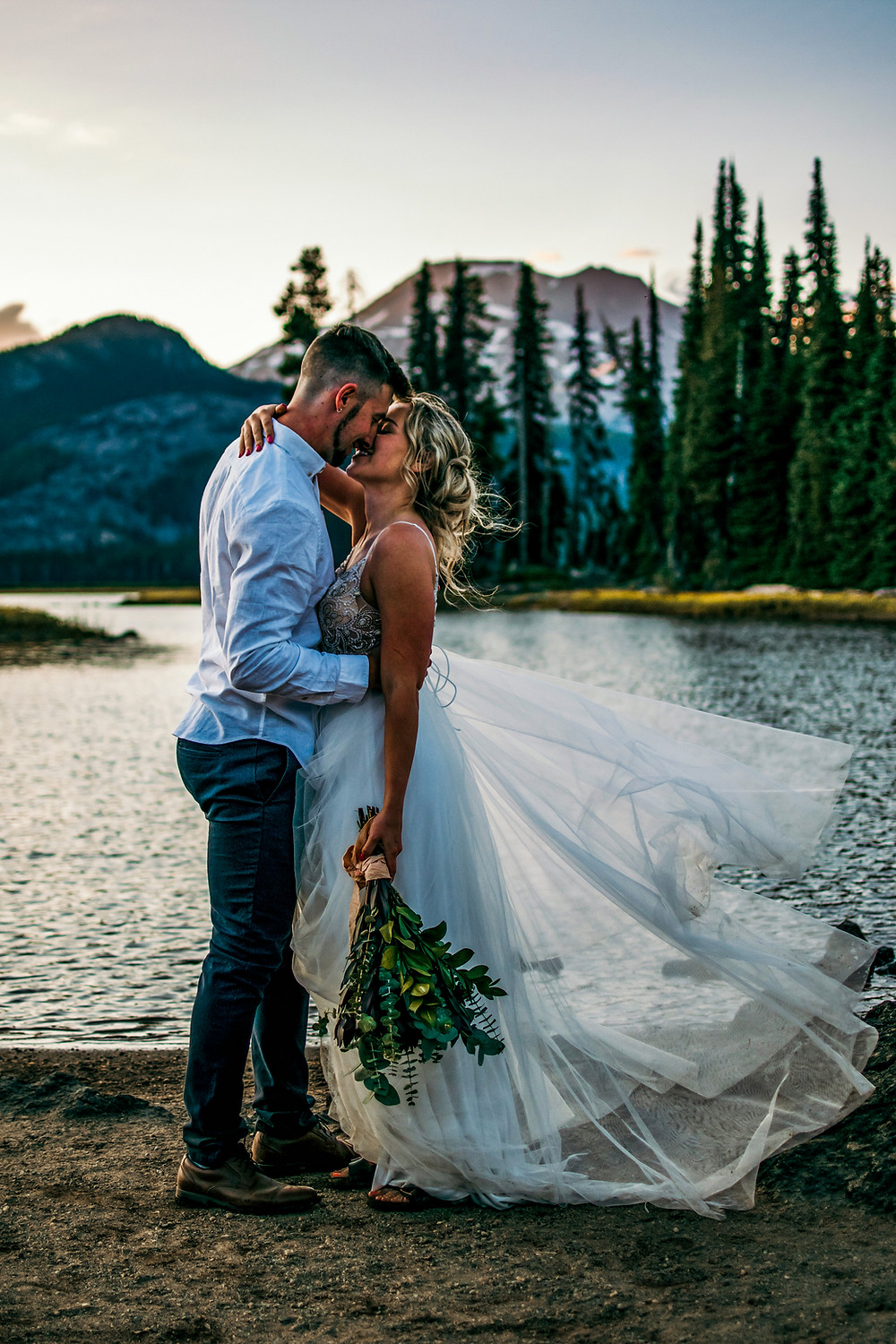 A couple kisses during their adventure elopement near mountains and a lake