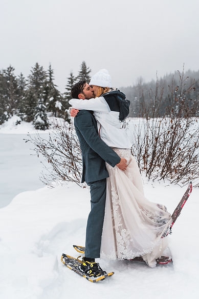 A couple kissing in the snow while snowshoeing at their magical Washington adventure elopement in the snow