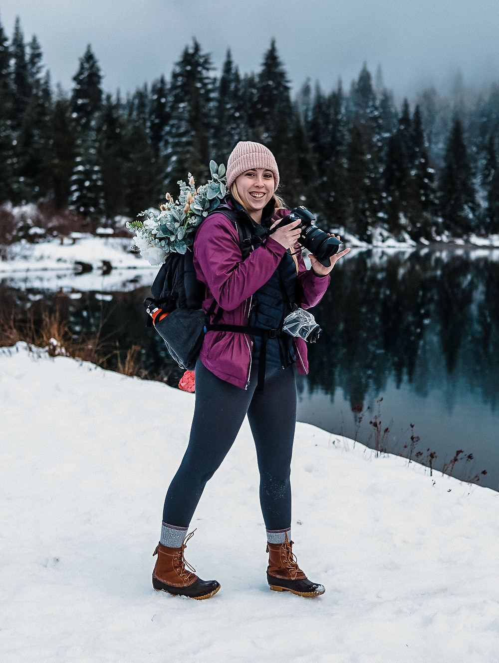 An adventure elopement photographer with a bridal bouquet in their backpack smiling while photographing an elopement in Washington