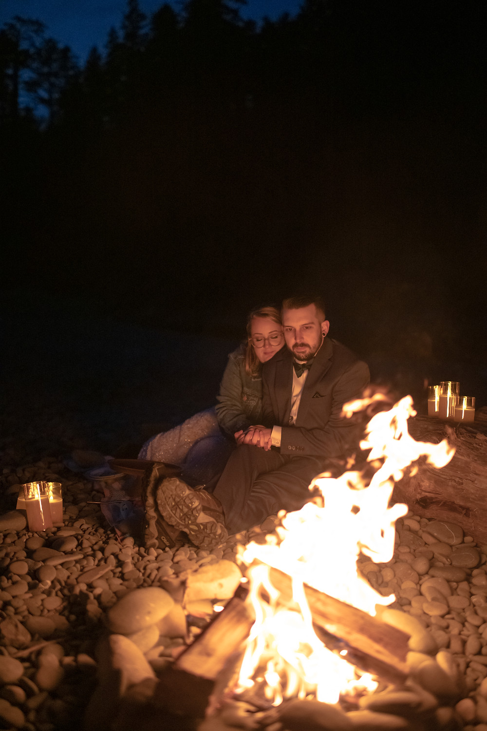 A couple on their elopement day in Olympic National Park sharing a campfire on the beach