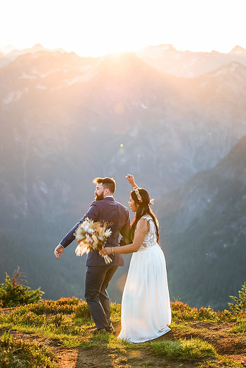A bride and a groom dancing on top of a mountain in the North Cascades on their elopement day in Washington at sunrise
