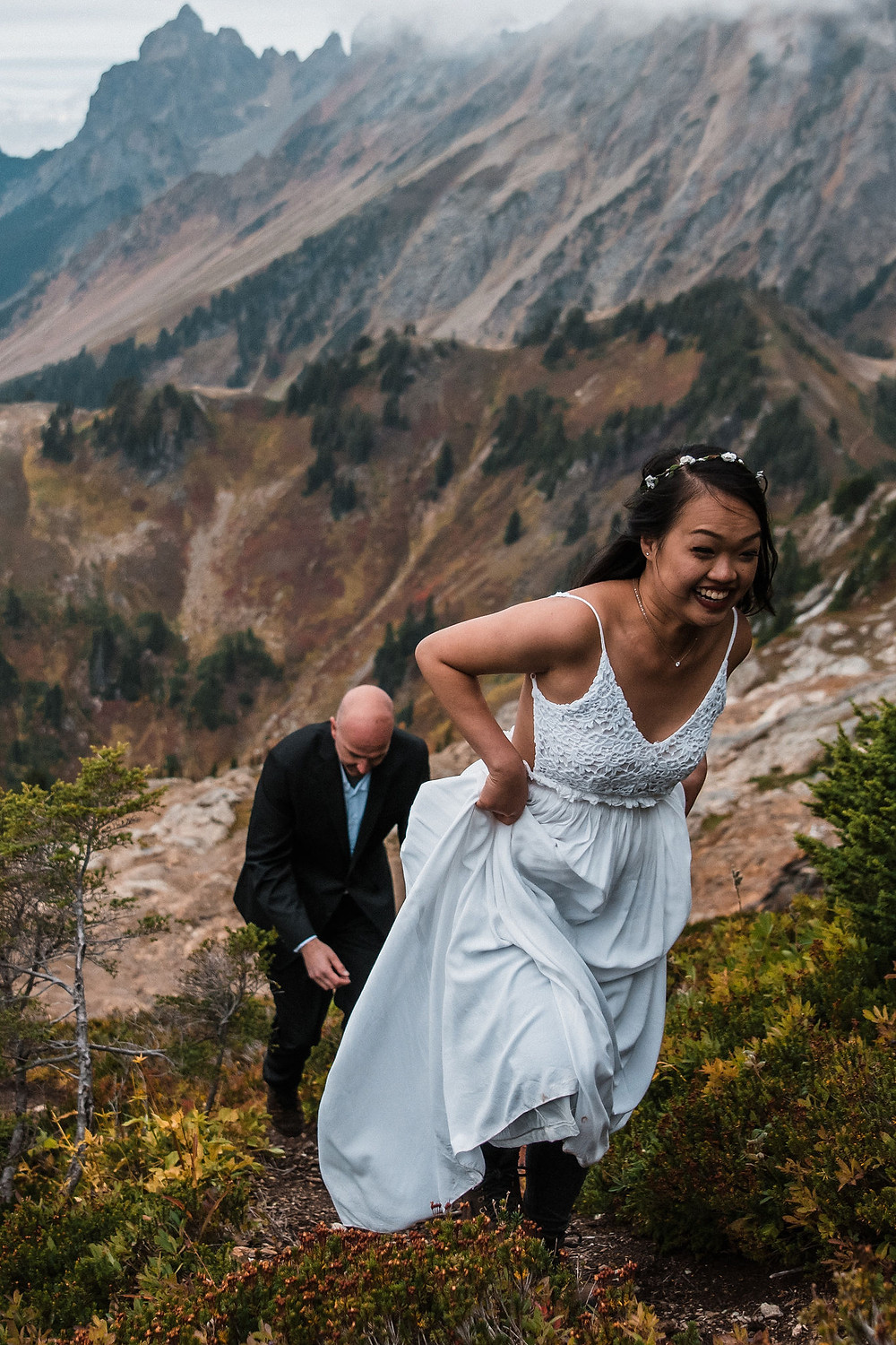A couple hiking up a mountain in the North Cascades on their wedding day in their wedding attire
