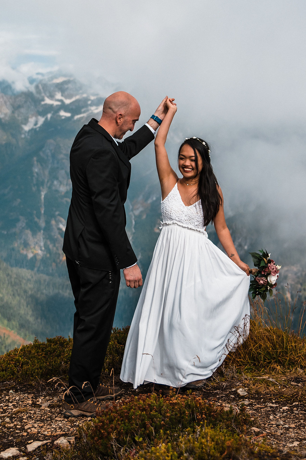 A couple dances on a mountaintop on their elopement day by Mount Baker