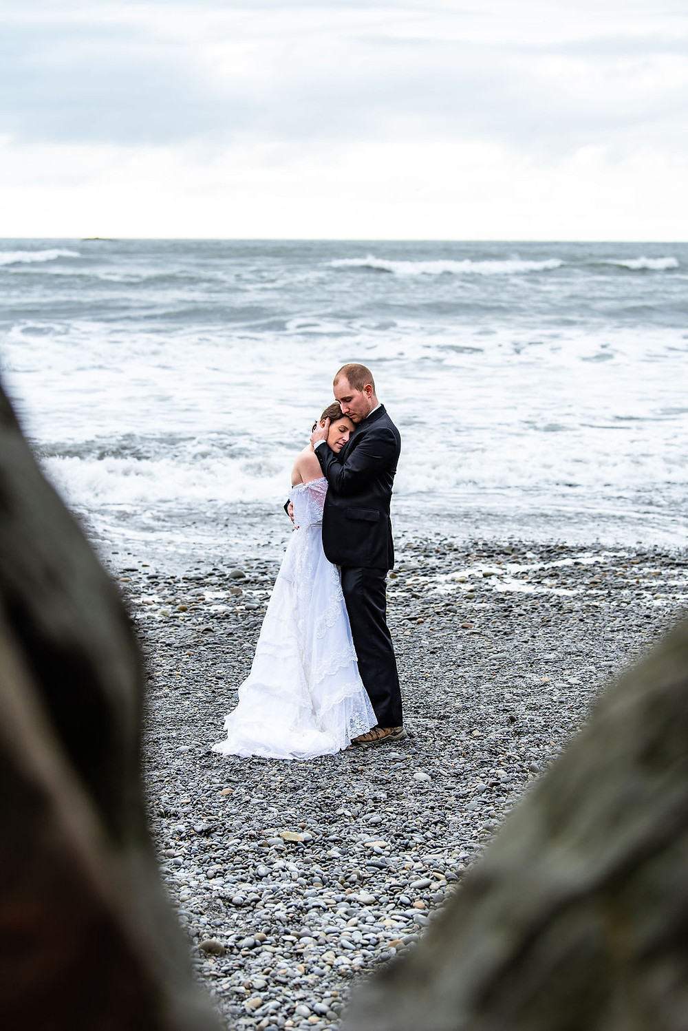 A groom hugs his bride on their adventure elopement day in Washington at Ruby Beach