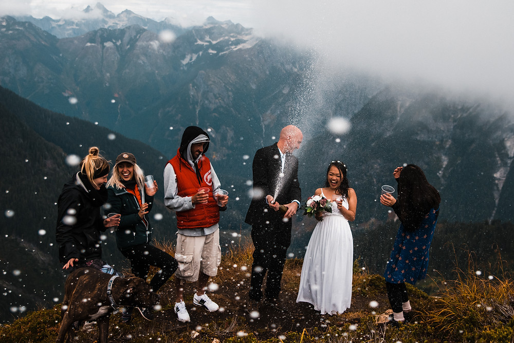 A couple and their closest friends popping celebratory champagne on the top of a mountain on their wedding day